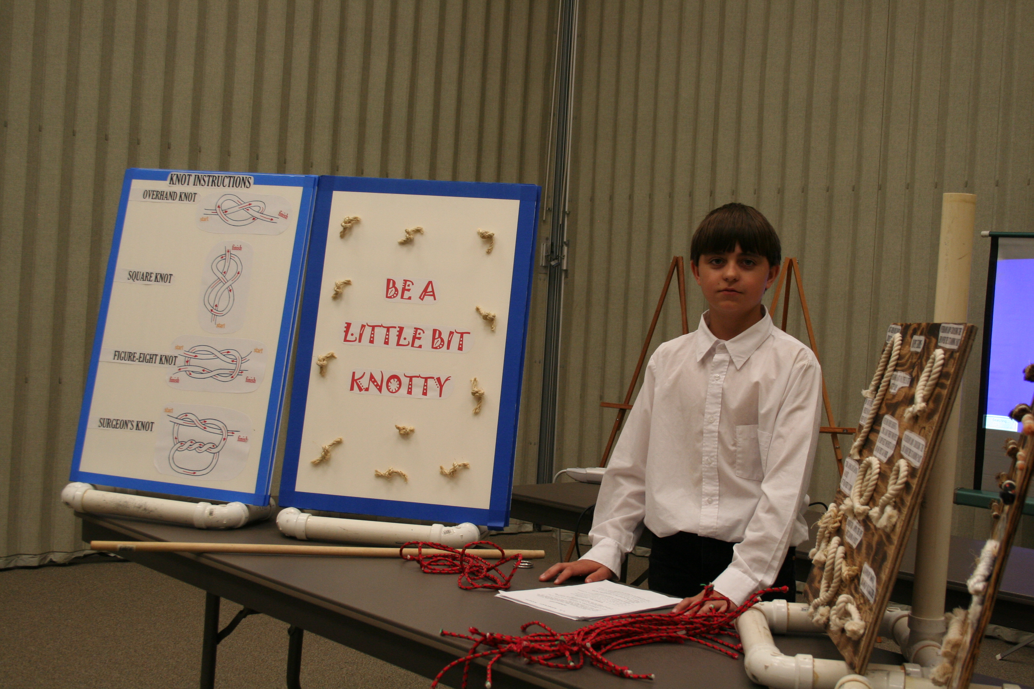 Young boy giving a demonstration on tieing knots.